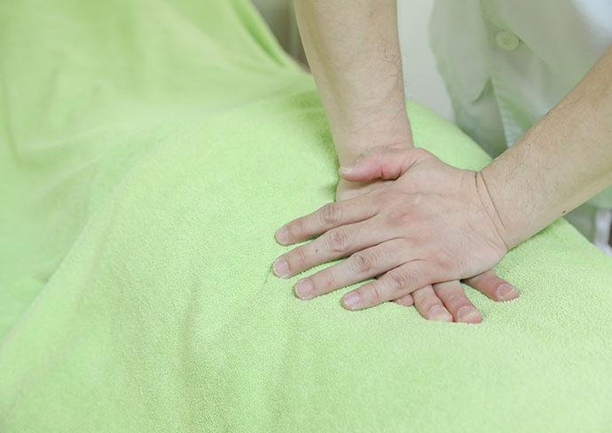タップ接骨院での整体治療で背中を指圧している様子